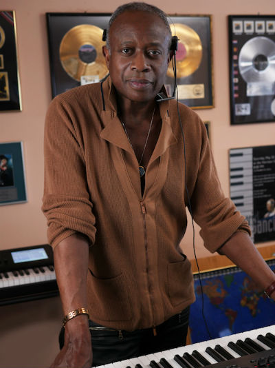 David Sancious standing at keyboard with albums in the background